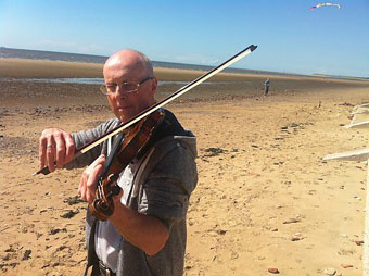 Richard playing violin on Crosby beach during the recording of BBC radio 4's WORD OF MOUTH - July 2014: Photo Credit: BBC